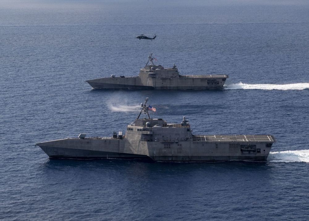 The Independence-variant littoral combat ships USS Gabrielle Giffords (LCS 10), bottom, and USS Montgomery (LCS 8) operate in the South China Sea, accompanied by an MH-60S Sea Hawk of Helicopter Sea Combat Squadron (HSC)