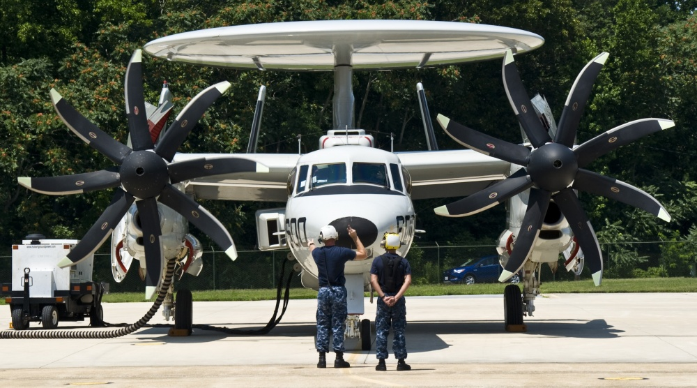 Aviation Structural Mechanic 1st Class Stephen Swett, left, and Airman Armando Braddy, assigned to the Pioneers of Air Test and Evaluation Squadron (VX) 1, signal for the start up of an E-2D Hawkeye on the flight line. (U.S. Navy photo by Mass Communication Specialist 2nd Class Kenneth Abbate/Released)