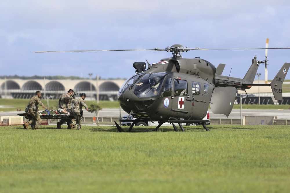 Soldiers from the Guam National Guard load a medical evacuation patient into a GUNG Lakota helicopter at Andersen Air Force Base on June 30.