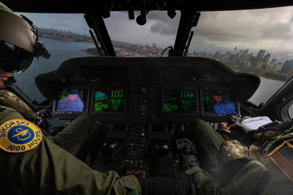 Royal Australian Navy officer, Lieutenant Benjamin Martin (left), RAN, and United States Navy officer, Lieutenant Commander Katie Stewart (right) fly an MH-60R Seahawk helicopter over Sydney Harbour during a photography exercise on the 18th September 2019.