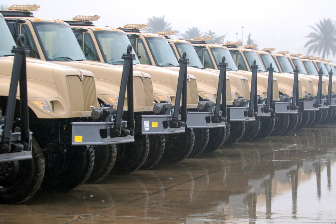 A portion of the 37 5-ton trucks delivered to the Iraqi Army Jan. 23 sit at Al Muthanna Vehicle Warehouse.