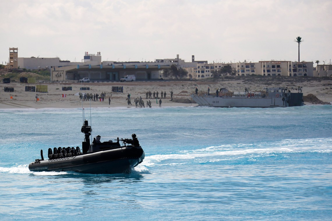 Egyptian troops come ashore by landing craft as a Royal Marines ORC patrols offshore.