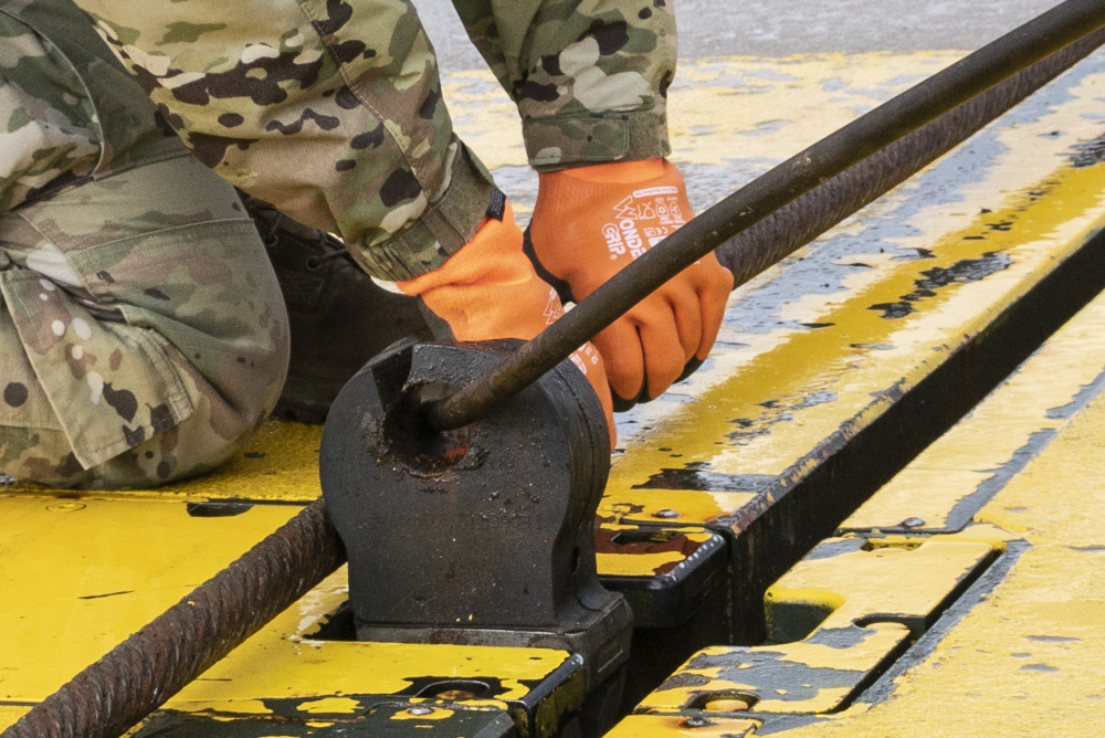 """U.S. Air Force Airman 1st Class Chelsea Glasscock, 435th Construction and Training Squadron Aircraft Arresting System Depot apprentice, returns the system to its starting position during a Barrier Arresting Kit certification at Ã""""mari AB, Estonia, March 17, 2021."""