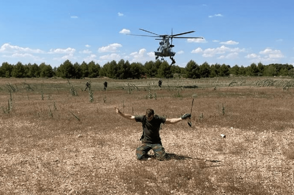 """An extraction team, supported by a helicopter, approaching the """"Isolated Person"""" during a recovery scenario on the RMC Flying Course. Photo courtesy Tactical Leadership Programme."""