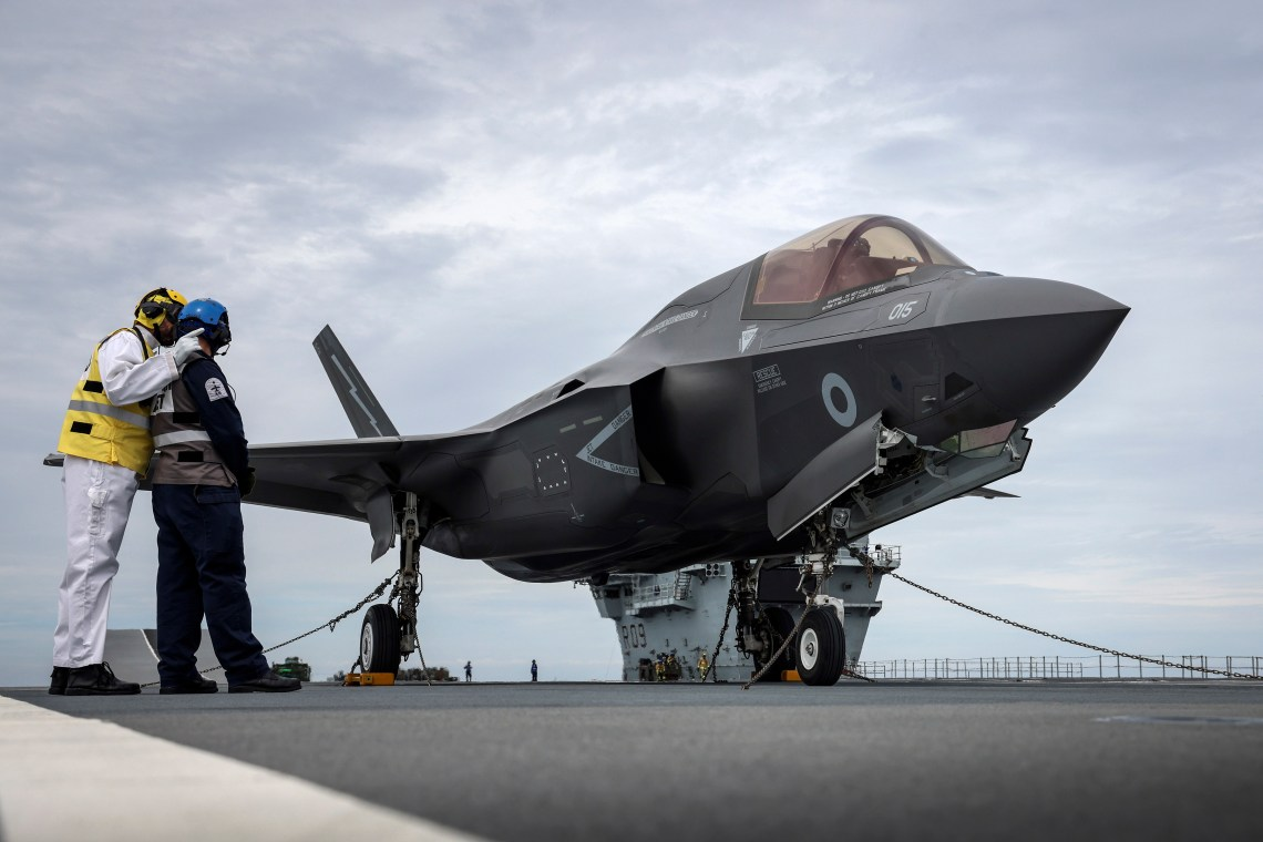 HMS Prince of Wales' Flight Deck Officer confers with an Air Engineer next to the first F-35 on deck.
