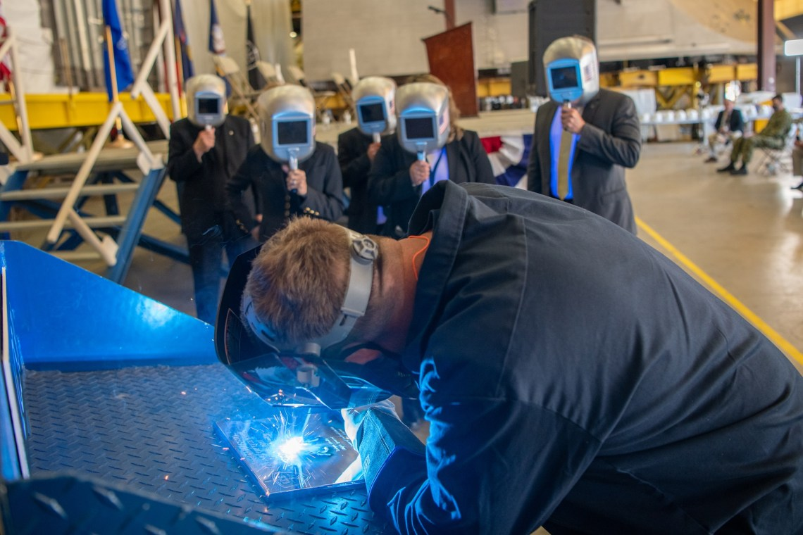 A welder authenticates the keel of Littoral Combat Ship (LCS) 31, the future USS Cleveland, by welding the initials of the ship's sponsor, Robyn Modly, wife of a Clevelander and former U.S. Navy Secretary, who has embraced the city as her own.