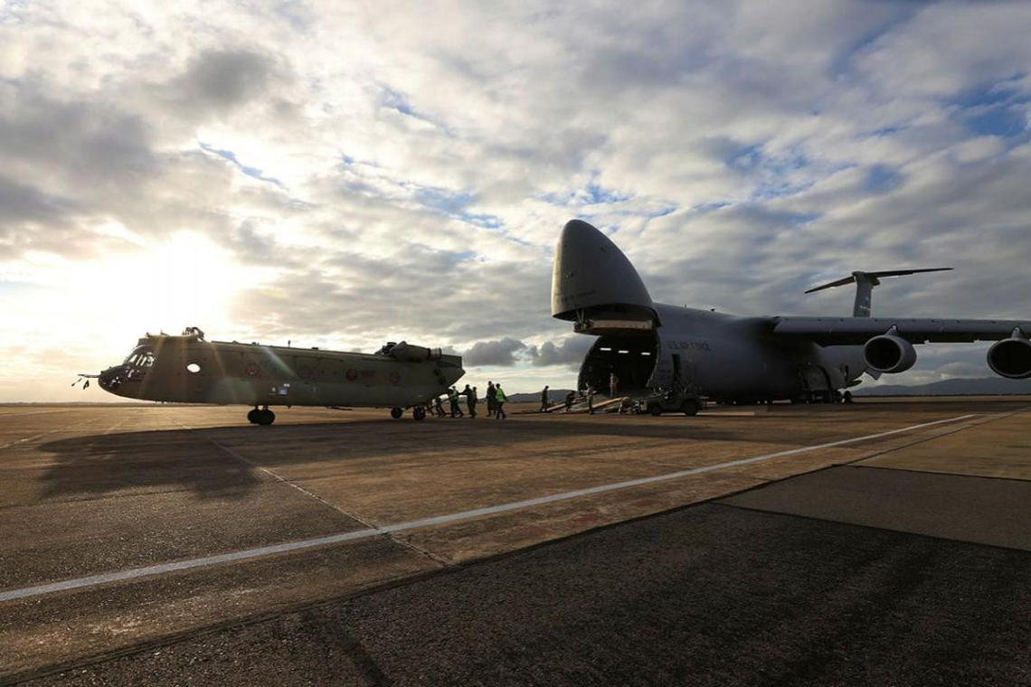 A new CH-47F Chinook heavy-lift helicopter is unloaded from a United Stated C-5 Galaxy at RAAF Base Townsville, Queensland.