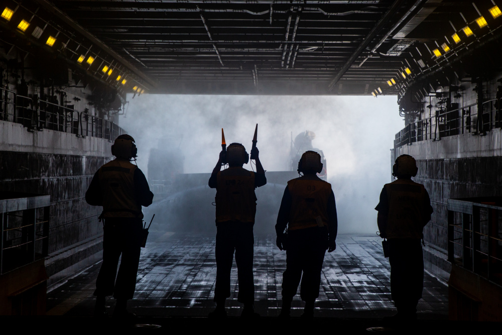 A U.S. Navy landing craft, air cushion is marshaled into the USS Arlington (LPD-24) carrying tactical vehicles during Defense Support of Civil Authorities (DSCA) mission rehearsals