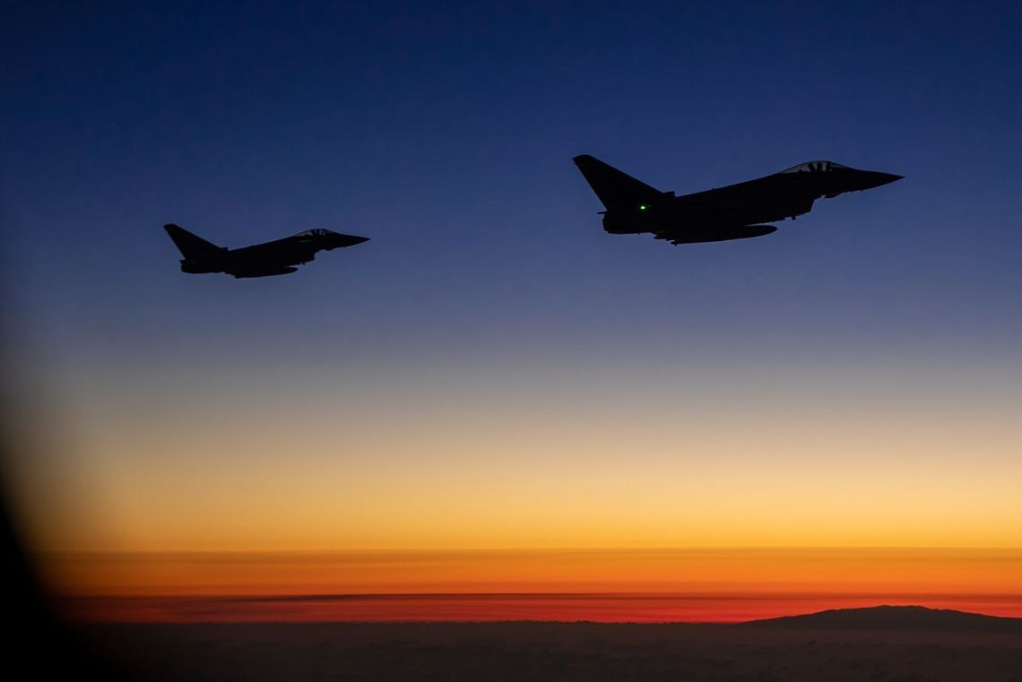 Two RAF Typhoon aircraft escort a Hercules C130 plane with members of the Pathfinders on board ready to conduct a parachute insertion.