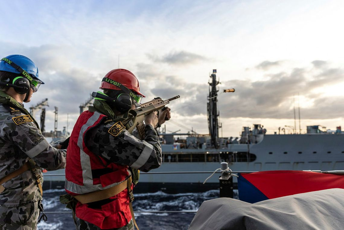 Able Seaman Boatswain's Mate Jacob Hodge (right) fires the line-throwing projectile during a Replenishment at Sea with USNS Rappahannock, off the coast of Queensland as part of Exercise Talisman Sabre 2021.