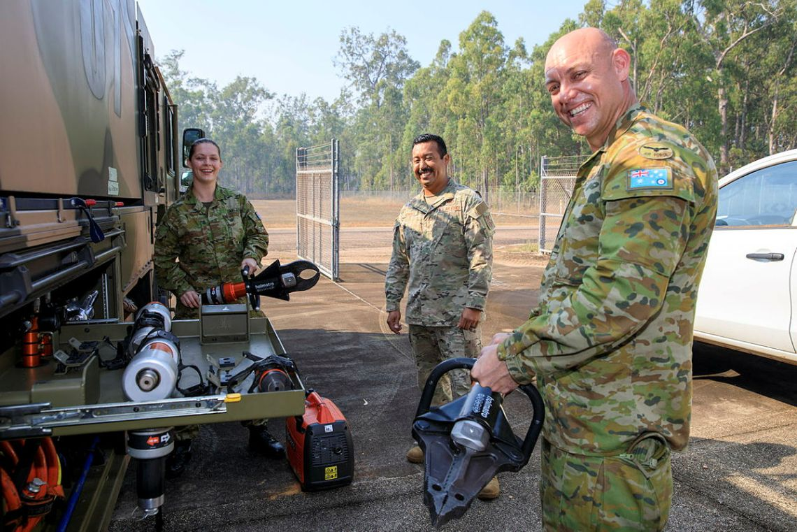 Aircraftwoman Amber Herz, US Army soldier Tech Sergeant Erik Montes and Leading Aircraftman Mitchell Houghton with rescue equipment from a Striker fire truck at RAAF Base Scherger, Queensland, during Exercise Talisman Sabre 2021.