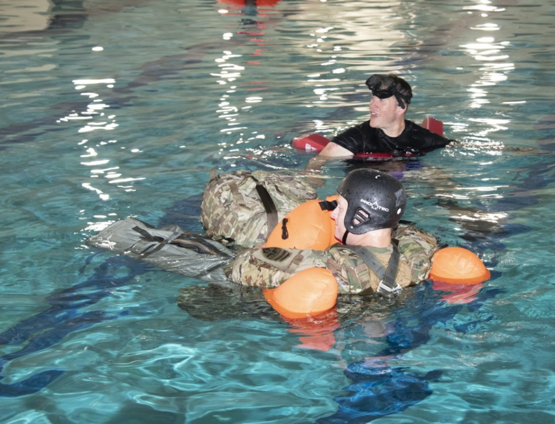 An Airborne and Special Operations Test Directorate test jumper conducts a combat equipment buoyancy test during the early stages of Parachutist Flotation Device (PFD) testing.