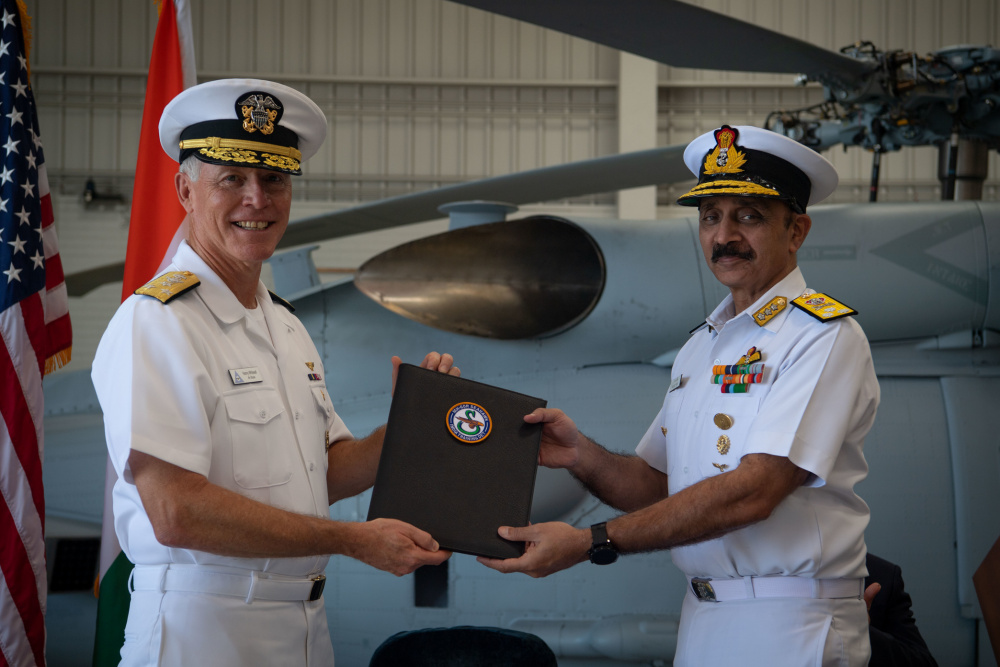 Vice Adm. Kenneth Whitesell, Commander, U.S. Naval Air Forces, left, presents the Material Inspection and Receiving Report for first aircraft to Vice Adm. Ravneet Singh, Indian Navy Deputy Chief of Naval Staff, during an acceptance ceremony at Naval Air Station North Island on Friday, July 16.
