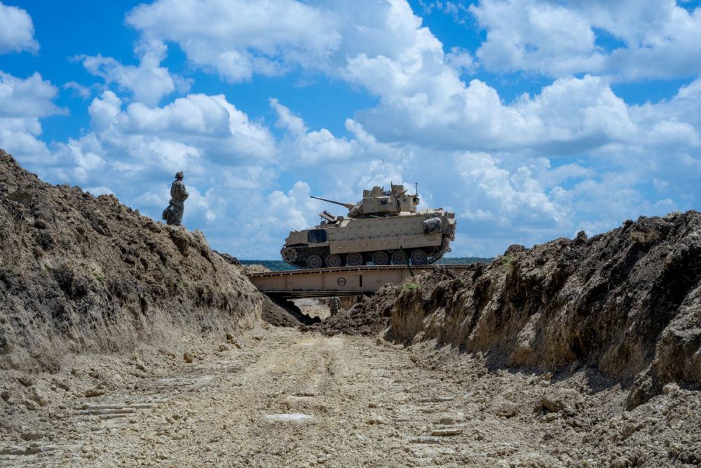 GREYWOLF Troopers with 3rd Brigade Engineer Battalion, 3rd Armored Brigade Combat Team, 1st Cavalry Division, dash across a Joint Assault Bridge (JAB) in a Bradley Fighting Vehicle during a combined arms breach exercise, Fort Hood, Texas, June 6, 2021.