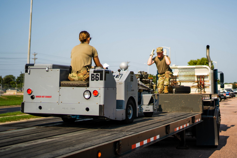 Senior Master Sgt. Steve Shade, 114th Logistics Readiness ground transportation superintendent, guides Staff Sgt. Jessica Ruiter, 114th Logistics Readiness air transportation/traffic manager, while driving a weapons loader onto a flatbed during the 2021 Readiness Exercise Aug. 8, 2021, at Joe Foss Field, S.D.