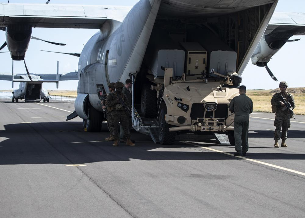 Artillery Marines from 1st Battalion, 12th Marines provide security as a Marine KC-130J loadmaster deploys a Navy Marine Expeditionary Ship Interdiction System launcher aboard Pacific Missile Range Facility Barking Sands, Hawaii, Aug. 15, 2021.