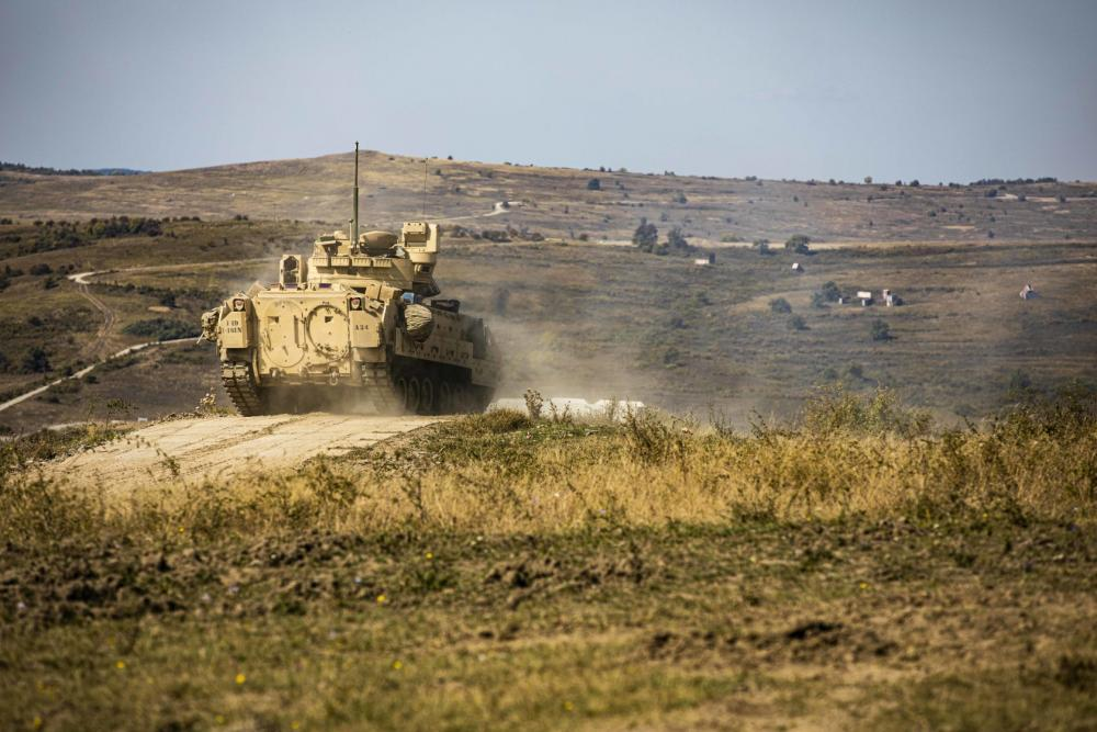 """U.S. Army Soldiers assigned to Alpha Company, 1st Battalion, 16th Infantry Regiment """"Iron Rangers,"""" 1st Armored Brigade Combat Team, 1st Infantry Division execute the Table V live-fire iteration for their Bradley Fighting Vehicle crew gunnery training at Land Forces Combat Training Center Getica in Cincu, Romania, Sept. 13, 2021."""