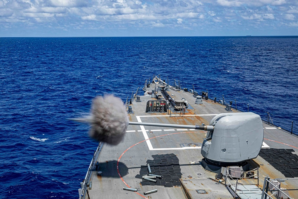 The Arleigh Burke-class guided-missile destroyer USS Curtis Wilbur (DDG 54) fires a 5-inch gun during a gunnery exercise. Curtis Wilbur is assigned to Commander, Task Force 71/Destroyer Squadron (DESRON) 15, the Navy's largest forward DESRON and the U.S. 7th Fleet's principal surface force.