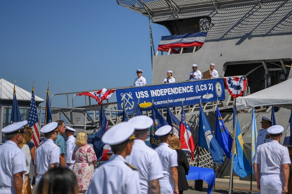 Ship's crew deliver the ensign and commissioning pennant during the decommissioning ceremony of littoral combat ship USS Independence (LCS 2).