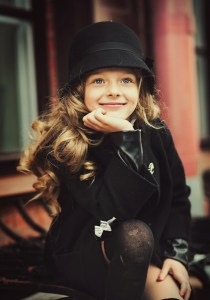 Happy baby girl in a black hat and coat smiling