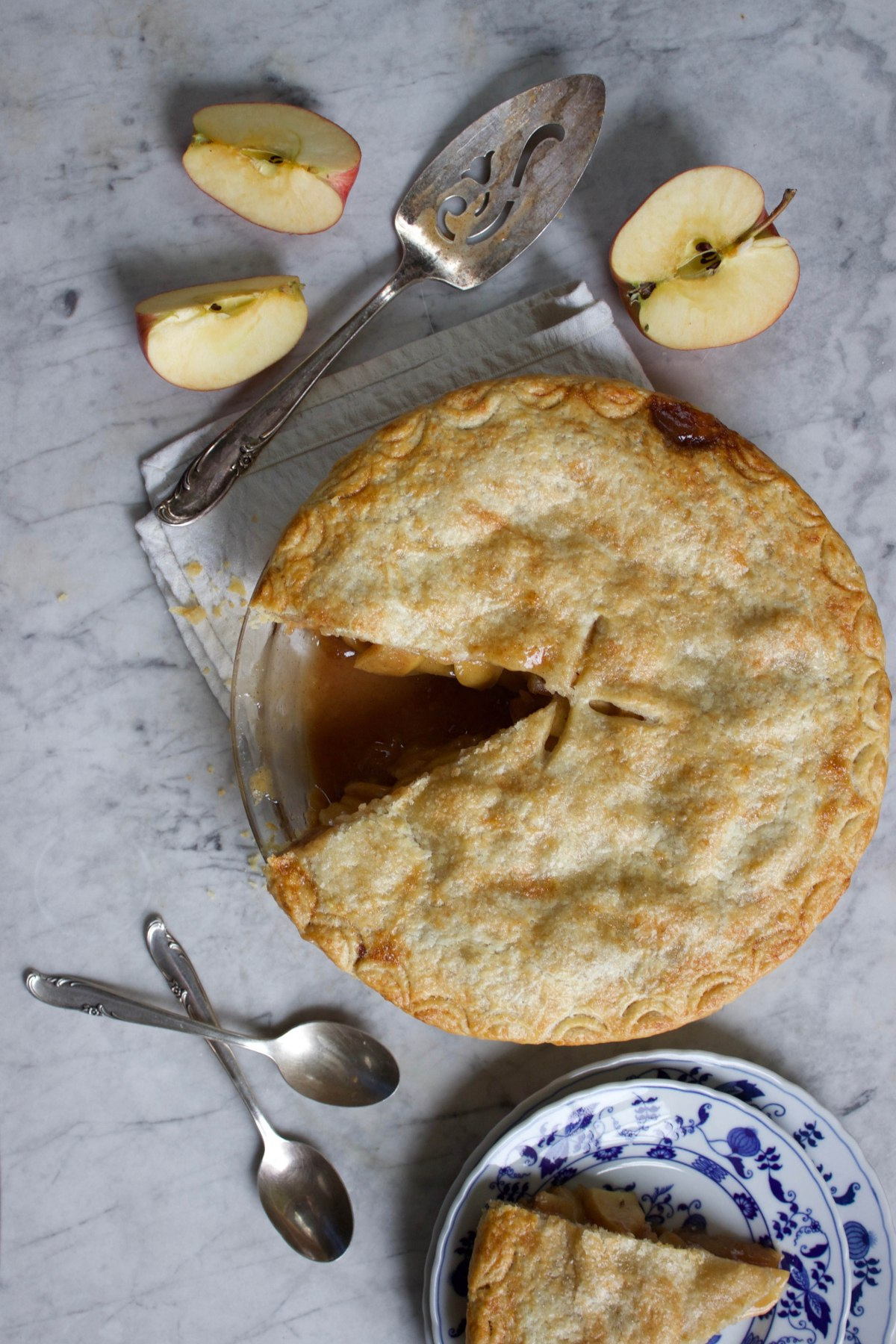 Apple pie resting on a marble surface beside sliced apples and two silver spoons.