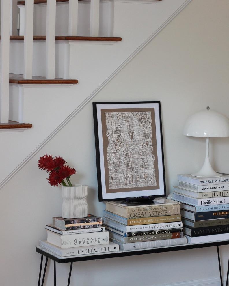 minimalist art over book stack - millay studio