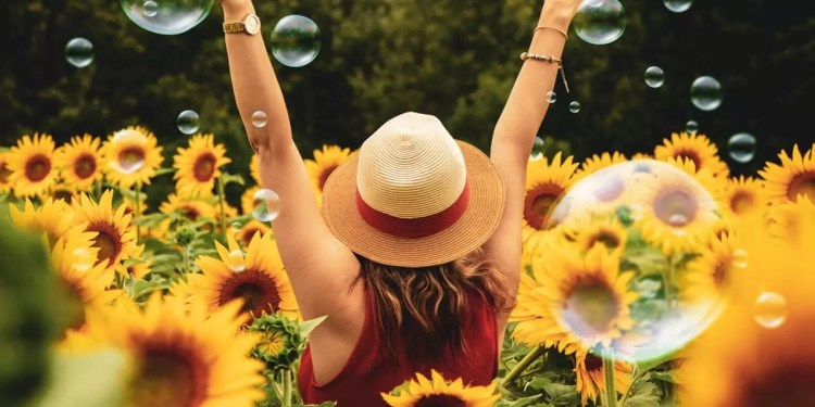 girl standing in a sunflower field with her arms up