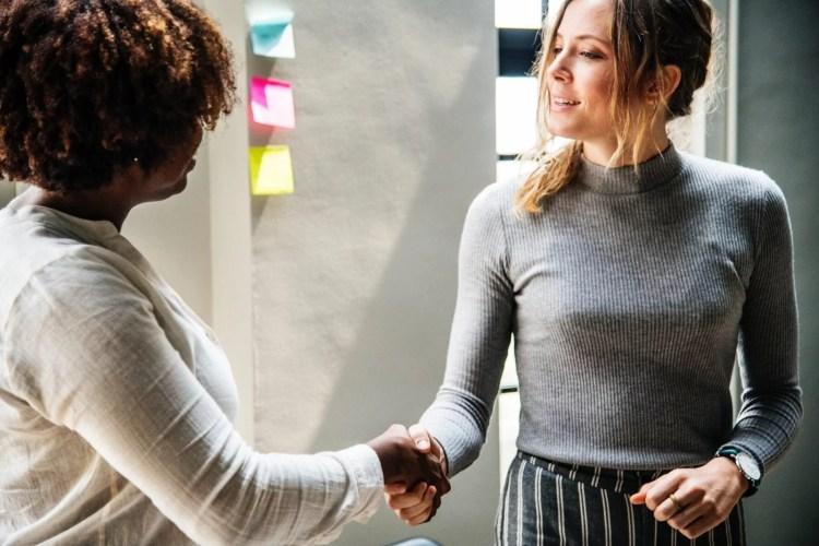 women shaking hands confidence