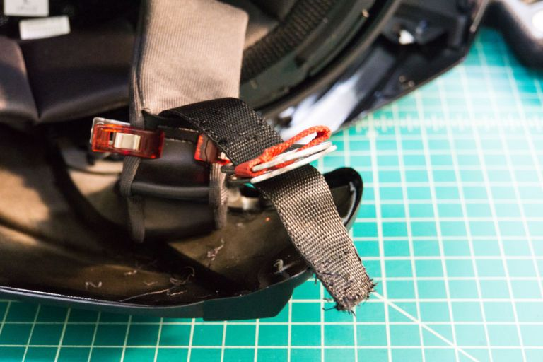 Undo the stitching to remove the d-rings from the original helmet strap.