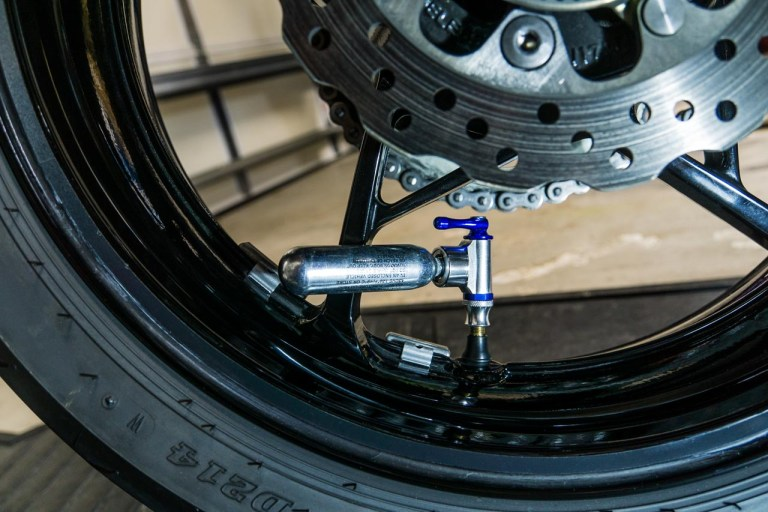 Though it's not without its downsides, a CO2 inflator is the most compact way to refill a tubeless motorcycle tire. Just keep in mind that you'll need multiple cartridges.