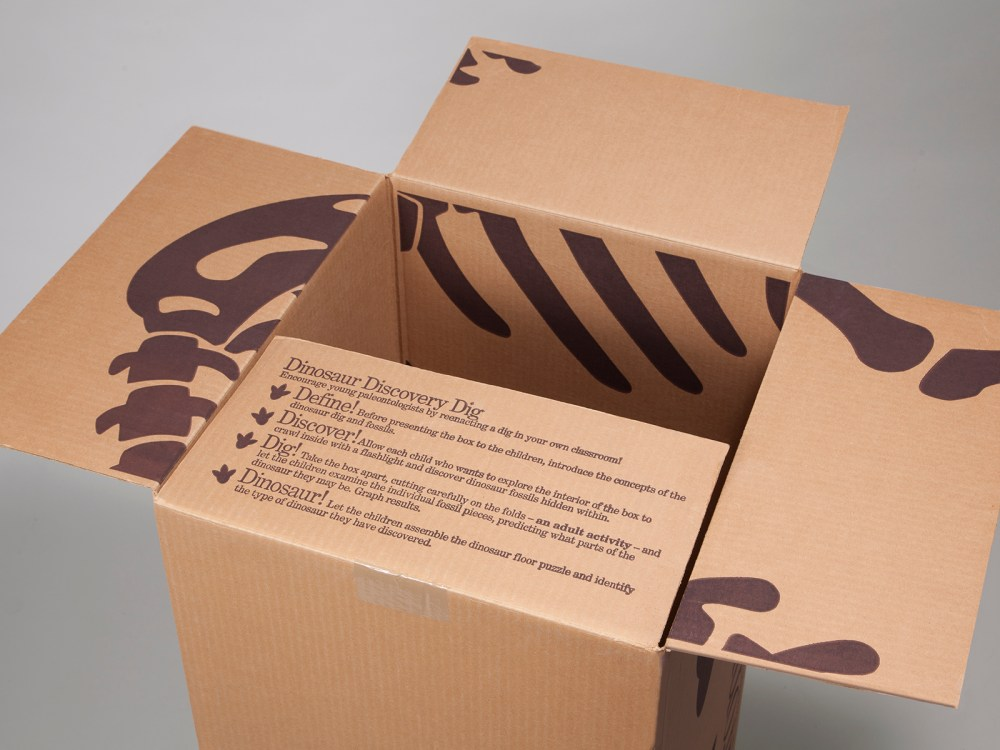 """Opening the box reveals instructions on a """"Dinosaur Discovery Dig""""."""