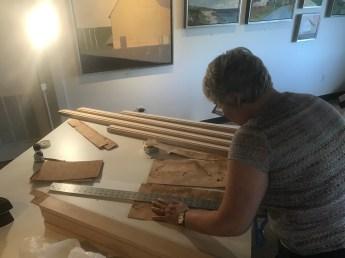 Measuring strips of veneer.