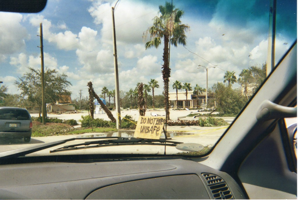 "View of strip mall from truck with ""Do Not Enter"" spray painted sign after Hurricane Katrina"