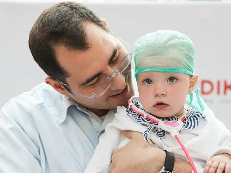 doctor holding baby milmedika pedijatar rade kaludjerovic