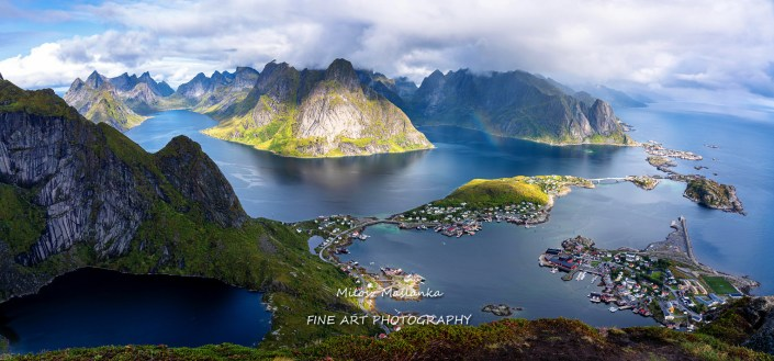 Sunny aerial panoramic view on stunning mountains and village of Reine in Lofoten islands, Norway from Reinebringen ridge. Scenic vista with a rainbow and rugged peaks.
