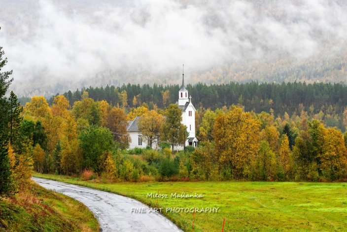 Lonely white church hidden among colorful trees