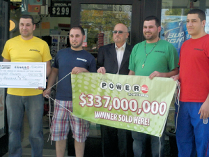 Lapeer Sunoco owners with Michigan Lottery DSR holding banner and bonus check