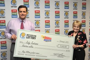 Michigan Lottery Commissioner M. Scott Bowen with $19 million Mega Millions jackpot winner Judy Juntunsen of Atlantic Mine holding the Big Check from the 2/5/2013 drawing.