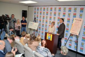 Powerball jackpot winner, Julie Leach, and Michigan Lottery Commissioner, M. Scott Bowen, speak with media members during a press conference in Lansing.