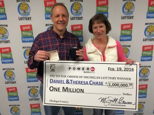 Daniel Chase holds his winning Powerball ticket and wallet while posing for a photo with his wife, Theresa.