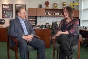Faye Valtadoros talks with Michigan State University basketball coach, Tom Izzo, after accepting her Excellence in Education award.