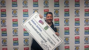Adam Jordan smiles after winning $500,000 playing the Hit $250 instant game.