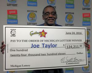 Joe Taylor of Flint smiles  with his big check for $124,211. His prize is half of the June 14 Fantasy 5 jackpot.
