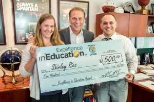 Shirley Ries poses for a photo with Riley Elementary principal, Joseph Corr, after accepting her Excellence in Education award from Michigan State University basketball coach Tom Izzo.
