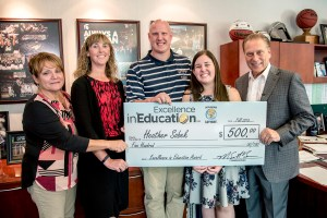 Heather Sobek poses for a photo with (left to right) Legg Middle School Assistant Principal, Dianne VandenHout, Legg Middle School Principal, Julie Slusher, and husband, James Sobek, after accepting her Excellence in Education award from Michigan State University basketball coach Tom Izzo.