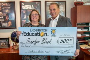 Jennifer Black poses for a photo after accepting her Excellence in Education award from Michigan State University basketball coach Tom Izzo.