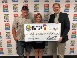 Melissa Cramer and her fiancee, Mark, pose for a photo with Lottery Commissioner, Aric Nesbitt, after collecting Cramer's $500,000 prize.