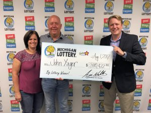 Lottery Commissioner, Aric Nesbitt, presents John Yager and his wife, Chris, with a check for $390,422.