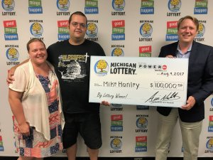 Lottery Commissioer, Aric Nesbitt, presents Mike Hanley and his wife, Mollie, with a check for Hanley's $100,000 Powerball prize.