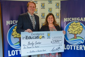 Becky Carter poses for a photo with Michigan Lottery Commissioner, Aric Nesbitt, after accepting her Excellence in Education Award.